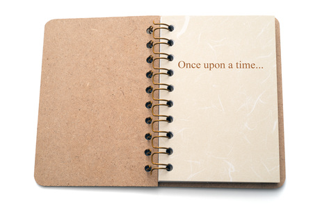 once: The text Once upon a time written on the first page of a notebook. Isolated on white background