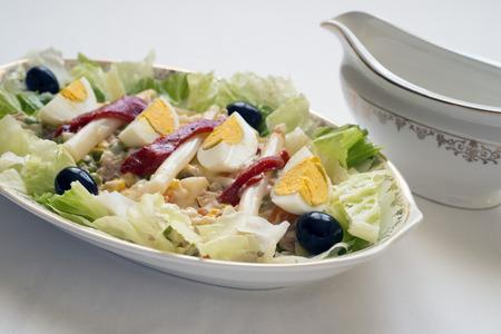 russian salad: bandeja de ensalada rusa y salsera en el fondo Foto de archivo