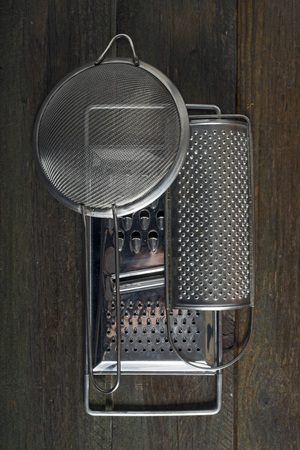drilled: Two kitchen graters and a strainer on a wooden table