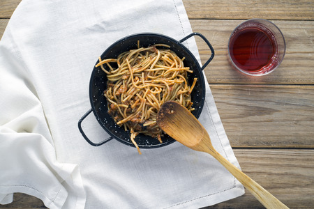 claret: Spaghetti with tomato sauce on wooden table. Not forgetting the glass of claret Stock Photo
