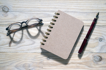 annotations: glasses, pen and notebook on wooden background Stock Photo