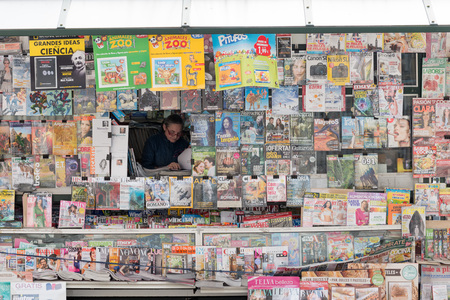 kiosk: SANTANDER, SPAIN - JANUARY 27, 2016: saleswoman from a kiosk full of magazines and newspapers, in Santander, Cantabria, Spain Editorial