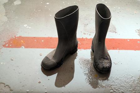 wellingtons: rubber boots on a wet cement floor