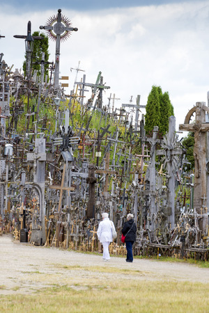 heaped: SIAULIAI, LITHUANIA - JUNE 9, 2016: Unidentified people at hill of crosses, Kryziu kalnas, Lithuania, a place of worship for Christians. Editorial