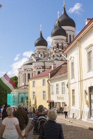 roofed house: TALLINN, ESTONIA- JUNE 12, 2016: Tourist in a central street in Tallinn, in the background domes Alexander Nevsky Cathedral, an Orthodox Cathedral in the Old Town Tallinn, Estonia.