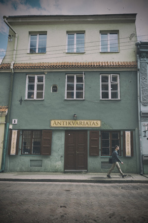 antiquarian: VILNIUS, LITHUANIA - JUNE 8, 2016: An unidentified man walks in front of an antiquarian shop. vintage processing