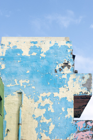 gutter: badly damaged facade of a house painted blue