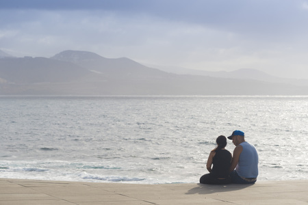 las palmas: LAS PALMAS DE GRAN CANARIA, SPAIN - AUGUST 1, 2016: A couple gazing out to sea at sunset from the promenade of Las Canteras in Las Palmas, Canary Islands Editorial