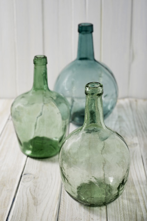 three bottles of green glass on a wooden background. selective focus Stock Photo