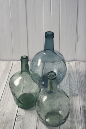 recipient: three bottles of green glass on a wooden background. vintage processing