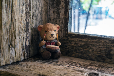 splintered: teddy on the windowsill of an old window Stock Photo