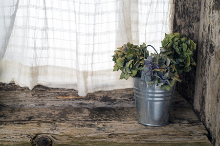 splintered: zinc bucket with dried hydrangea flowers on a window sill Stock Photo