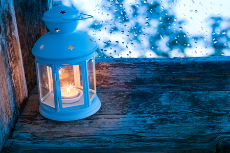 embrasure: lighted lantern on a window sill