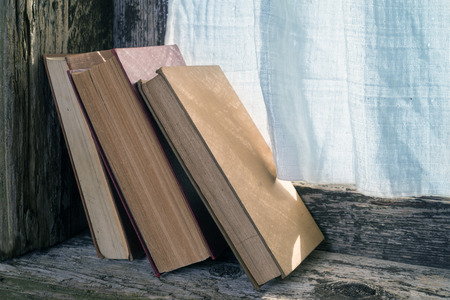 embrasure: books on the windowsill of an old wooden window