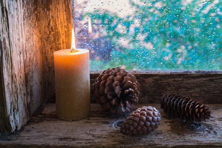 sill: lit candle and pine cones on a window sill. Christmas ornament