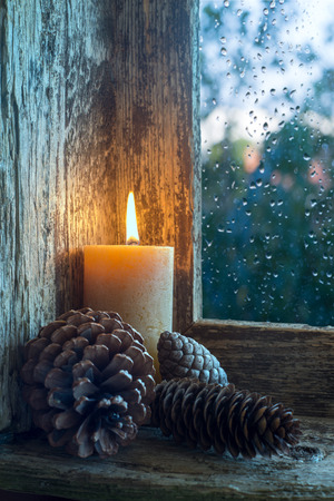 splintered: lit candle and pine cones on a window sill. Christmas ornament