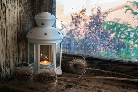 splintered: lighted lantern and Dry thistles on the sill of a window. Christmas ornament