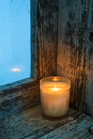 splintered: Burning candle on the sill of a window. Christmas ornament