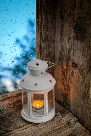 splintered: lighted lantern on a window sill