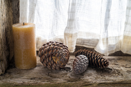 pinecones: three pinecones and a candle on the windowsill of an old window