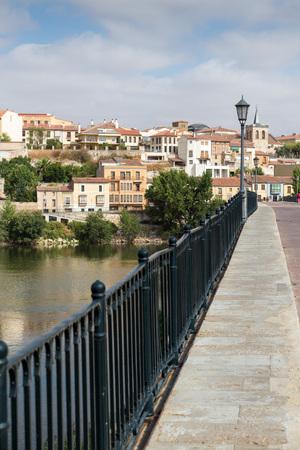 castille: Stone bridge over Douro river and Zamora city in background.