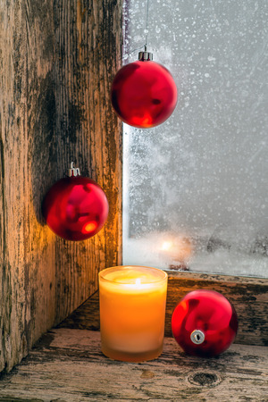 lit candle and Christmas balls on the windowsill of an old window with frosted glass Stock Photo