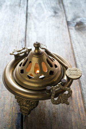 brazier: flame in a bronze brazier on wooden table
