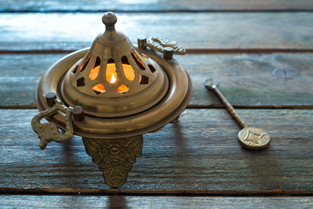 embossment: flame in a bronze brazier on wooden table