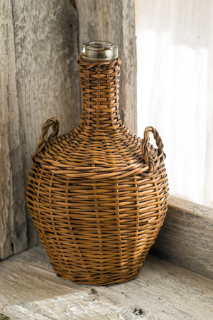 bulrushes: Old lined wicker bottle on the sill of a window