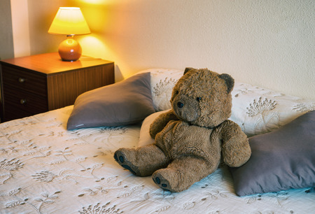 bedside lamps: Happy teddy bear relaxing on comfortable bed Stock Photo