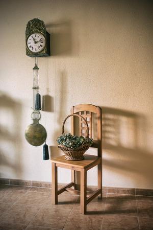 reloj de pendulo: un viejo reloj de péndulo y una cesta de flores secas en una silla. Alegoría del tiempo. procesamiento de la vendimia Foto de archivo