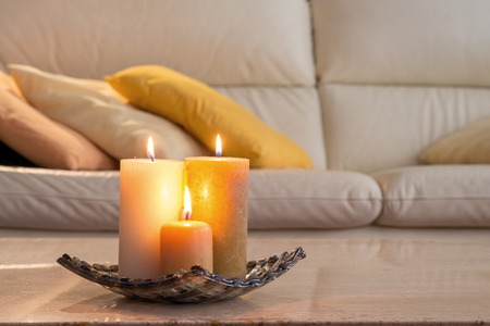 room decoration: lit candles on a marble table and in the background a sofa with pillows, which