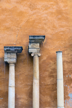 roman pillar: columns and capitals in front of a wall painted ocher Stock Photo