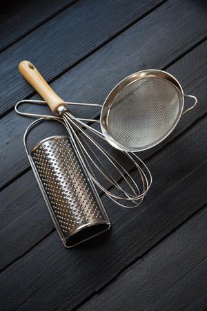 utensilios de cocina: utensilios de metal sobre madera negro Foto de archivo