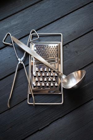 cookware: utensilios de metal sobre madera negro Foto de archivo