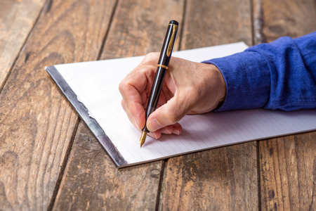 dispositions: mans hand writing with a fountain pen. wooden background