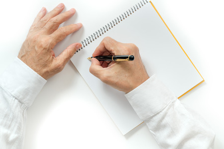 mans hand writing with a fountain pen. isolated