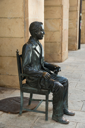 arcades: SORIA, SPAIN - NOVEMBER 2, 2016: Sculpture of the writer Antonio Machado next to the arcades of the Institute that bears his name in Soria