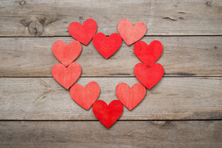 smaller: Heart formed with smaller hearts. Wooden background