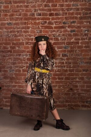 the Girl in army dress in hand with suitcase