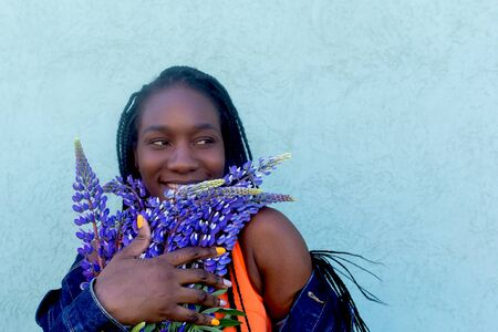the Happy and beautiful African American with purple flowers