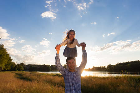 the Happy Dad with Daughter at Sunset
