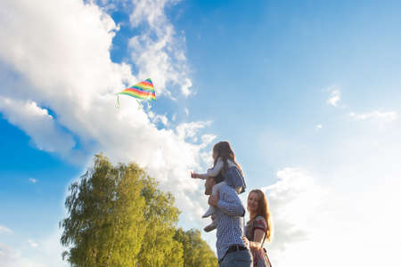 Family launches kite against beautiful sky 版權商用圖片