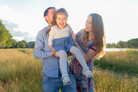 Happy young family walks in nature, at sunset