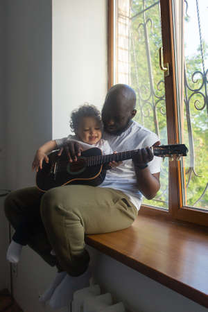 the Dad plays guitar to son song, Afro Amercans 版權商用圖片