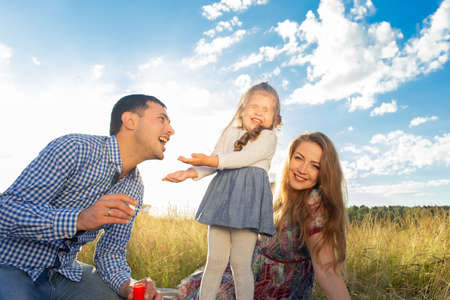 the Happy young family walks in nature, at sunset