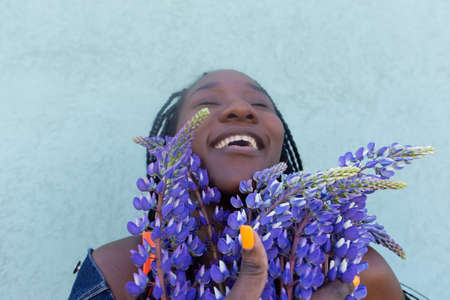 the happy African-American woman with grey flowers