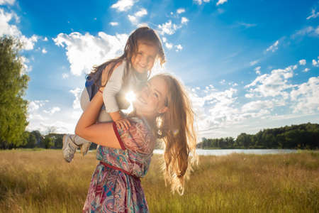 the Happy mom with daughter against beautiful sky