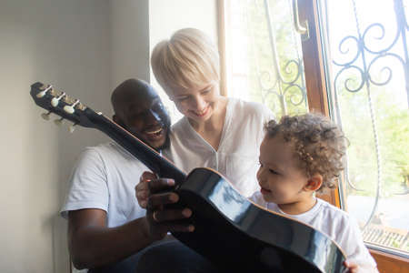 the Toddler plays guitar with mom