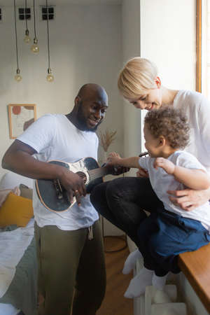 the Dad plays guitar to little son, multinational family